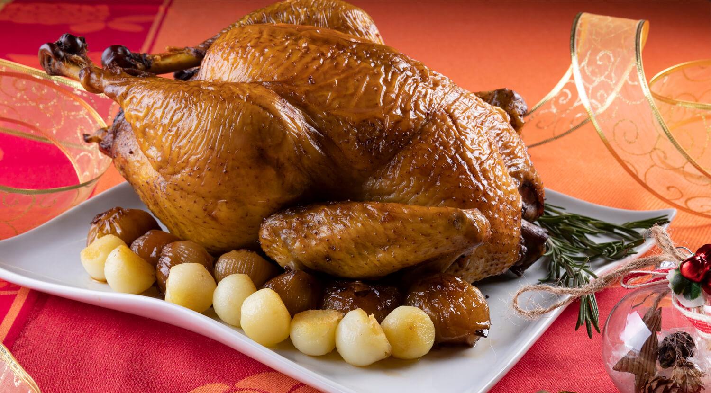 pollo entero en plato, servido con cebollitas
