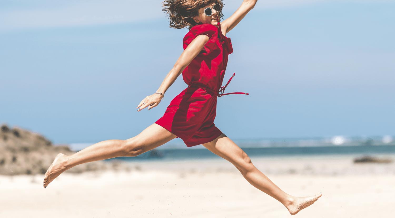 chica saltando en la arena de la playa