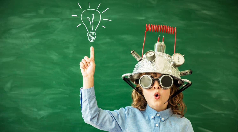 niño frente a pizzarra con casco de inventos